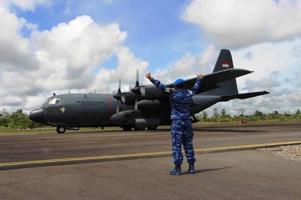 Petugas TNI AU memberi aba-aban saat pendaratan Pesawat Hercules di Dekai