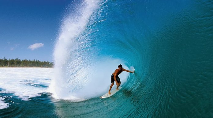 Seorang turis tengah surfing di pantai Wafor